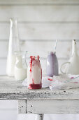 A milk shake with berry sauce on a white wooden surface