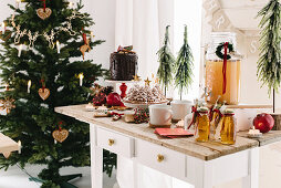 Hot apple punch, bundt cake and drip cake on dessert buffet in front of Christmas tree