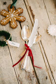 Silver cutlery tied with red velvet ribbon and gingerbread biscuit on wooden surface