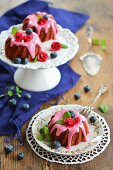 Three mini gugelhupfs with beetroot, frosting, sugar flowers, fresh blueberries and mint