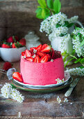 Strawberry profitrole cake with cream cheese mousse and strawberry cream inside profitroles