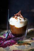 A glass of coffee with cream and chocolate