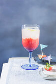 A cocktail made with gin, lemon and strawberries