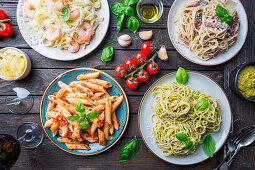 Several plates of pasta with different kinds of sauce over wooden background (Italian food)