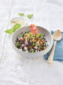 Quinoa salad with beans, goat's cheese, raw ham and hazelnuts