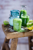 Green smoothies with ingredients on a wooden stool