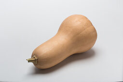 A butternut squash on a white surface