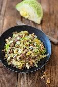 Savoy cabbage with minced meat and walnuts in a pan