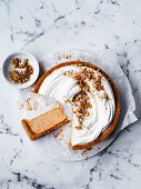 Raw carrot cake topped with cream and chopped walnuts