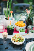 Guacamole and potted succulents on table set for Mexican party