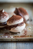 Macaroons with chocolate cream and cocoa powder