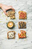 Vegane Vollkorntoasts belegt mit Obst, Samen, Nüssen und Erdnussbutter zum Kaffee