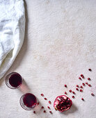 Glasses of red wine and pomegranate wedges with seeds on a white surface