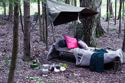 Cushions and blankets on vintage camping bed in woods