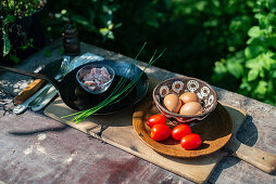 Ingredients for making scrambled eggs on a garden table