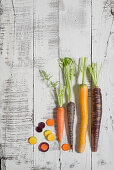Various different coloured carrots on a white wooden surface