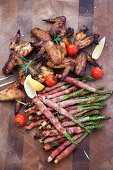 Smoked chicken wings and green asparagus with grilled ham
