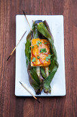 Grilled tofu with asparagus and cheese wrapped in a banana leaves