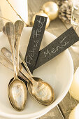 Old silver spoons and labels in a white bowl on a Christmas table