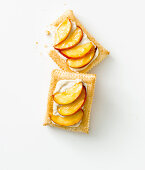 Puff pastry slices with peaches, yoghurt cream and almonds