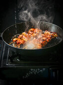 Steaming chicken skewers in a grill pan
