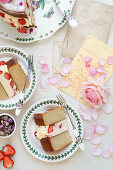 Romantic strawberry and rose layer cake on vintage plates with roses