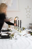 Woman lighting candles on festively set table