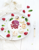 Russian cottage cheese cakes with berry jam, almonds, fresh raspberries and mint over