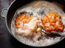 Breaded escalope being fried in butter (Viennese escalope)