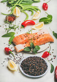 Raw uncooked salmon fish fillet steaks with vegetables, greens, rice and spices over grey marble background