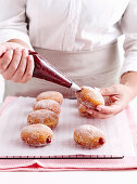 Filling Doughnuts with jam