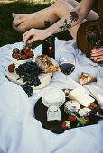 A cheese platter with strawberries, red wine, grapes and bread on a picnic blanket