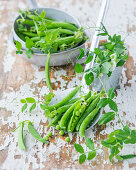 an arrangement of peas with flowers and a draining spoon