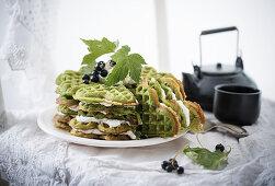 Matcha waffle cake with vanilla cream and fresh blackcurrants