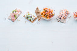 Fruity crispbreads and melon balls with ham cubes