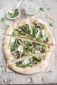 Vegan pizza with pesto, asparagus, courgette, mushrooms and pine nuts