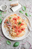 Spaghetti with tomato sauce, fresh basil and grated parmesan cheese