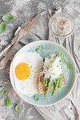 Breakfast toast with asparagus, grated parmesan and fresh basil, served with fried egg