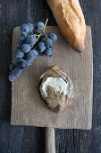 Blue cheese with oak leaves, a baguette, and a bunch of grapes