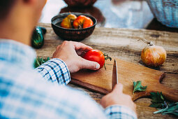 A man chopping a tomato