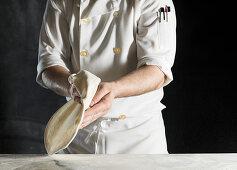 A chef baking pizza dough