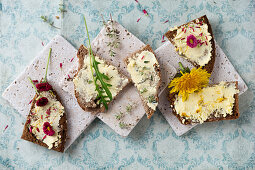Dandelion and daisy butter, thyme butter, and dandelion butter on slices of bread