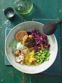 A Buddha Bowl with quinoa fritters, orange and red cabbage salad, mushrooms and edamame beans