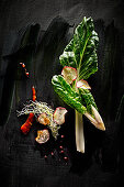 Food art: chard with red celery, pink pepper, beansprouts and chilli sauce on a black surface