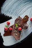 Food art: chocolate with raspberries, mint and chopped hazelnuts and nougat pralines on a painted surface