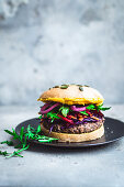 Black bean burgers with colourful toppings and hummus