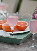 Brunch outside, flowers, glasses of sparkling pink lemonade, grapefruit halves on an outdoor table