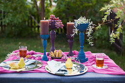 Table festively set in blue and purple in garden