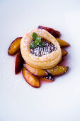 A mini damson tart with puff pastry on roasted damsons