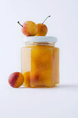 A jar of yellow plum jam against a white background